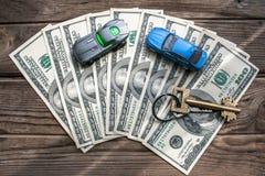 与一个回归键的一百美元钞票和在木背景的两辆玩具汽车 库存图片