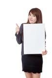 与一个垂直的空白的标志的亚洲女实业家翘拇指 免版税库存照片