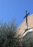 与一个基督教会的十字架的橄榄树 免版税库存照片