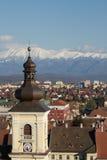 与一个塔在前景和山的冬天风景在背景中 免版税图库摄影