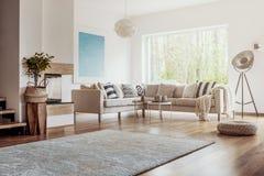 与一个大地毯的露天场所,白色客厅内部在黑暗,硬木地板和一个米黄壁角沙发有坐垫的 库存图片