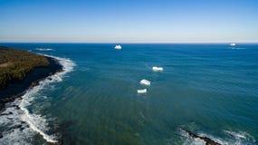 与一个大孔的鸟瞰图冰山和Ferryland冰山在背景,纽芬兰 免版税库存图片