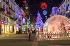 与一个大玻璃球的圣诞节装饰照亮的步行街道在前景 库存照片