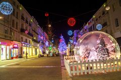 与一个大玻璃球的圣诞节装饰照亮的步行街道在前景 免版税库存图片
