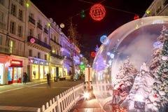 与一个大玻璃球的圣诞节装饰照亮的步行街道在前景 图库摄影