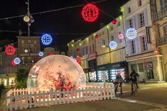与一个大玻璃球的圣诞节装饰照亮的步行街道在前景 库存图片