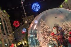 与一个大玻璃球的圣诞节装饰照亮的步行街道在前景c 免版税库存照片