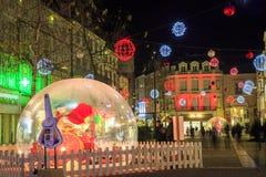与一个大玻璃球的圣诞节装饰照亮的步行街道在前景c 免版税库存图片