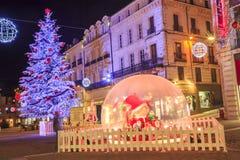 与一个大玻璃球的圣诞节装饰照亮的步行街道在前景c 库存图片