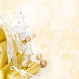 与一个天使的金黄被包裹的圣诞节礼物在木backgr 库存图片
