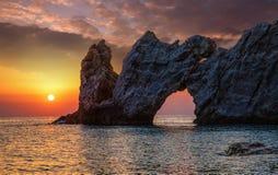 与一个孔的美妙的岩石在日落的海 免版税库存照片