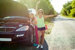 与一个孩子的一个妇女司机一条乡下公路的,在一辆残破的汽车附近 库存图片