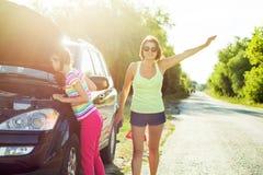 与一个孩子的妇女司机一条乡下公路的,在一辆残破的汽车附近 免版税库存照片