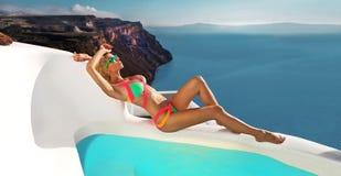 与一个完善的身体的美好的女性白肤金发的模型和在圣托里尼海岛上的惊人的长的头发在希腊 免版税库存图片