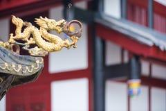 与一个寺庙大厦的金黄色的龙雕塑在ba 免版税库存照片