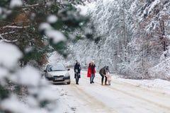与一个小婴孩的乐趣公司在冬天杉木下的雪道的 图库摄影