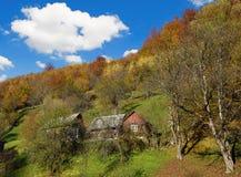 与一个小屋的神秘的风景在小山在秋天在backgro 免版税库存照片