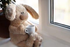 与一个小杯子的软的玩具兔宝宝 免版税库存图片