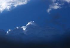 与一个小白色云彩边缘的深蓝动乱的预兆 免版税图库摄影