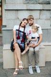 与一个小美丽的婴孩的年轻愉快的家庭有蓝眼睛的,与大厦的灰色 母亲和女儿 库存照片