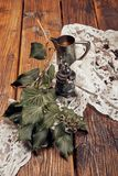 与一个小金属咖啡罐、一个金属糖杯子、咖啡豆和常春藤的静物画在一张老木桌上 库存照片