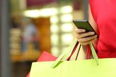 与一个巧妙的电话的顾客购物 免版税库存照片