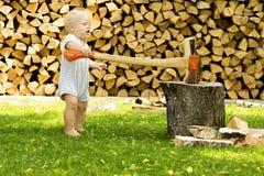 与一个巨大的轴的滑稽的小孩切口firewoods 免版税库存图片