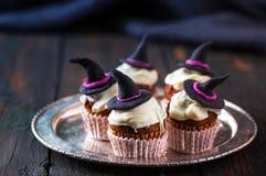 与一个巫婆帽子的杯形蛋糕在板材 图库摄影