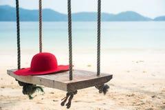 与一个帽子的木摇摆在热带海滩为夏天和假期 免版税库存照片
