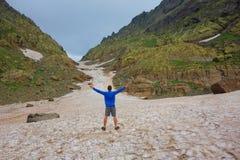 与一个年轻人的供徒步旅行的小道在高加索山脉的一个多雪的Tobavarchkhili山口的在变成银色湖的远足的乔治亚 库存照片