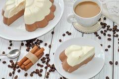 与一个开胃奶油甜点层数(香草和巧克力)蛋糕和一个杯子的一个盘木表面上的牛奶咖啡 库存图片