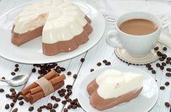 与一个开胃奶油甜点层数(香草和巧克力)蛋糕和一个杯子的一个盘木表面上的牛奶咖啡 库存照片