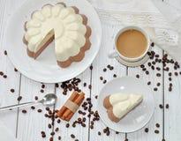 与一个开胃奶油甜点层数(香草和巧克力)蛋糕和一个杯子的一个盘木表面上的牛奶咖啡 免版税库存照片