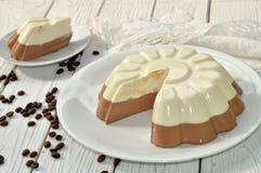 与一个开胃奶油甜点层数(香草和巧克力)蛋糕的一个盘木表面上装饰用咖啡豆 库存照片