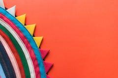 与一个弯曲的三角边缘的明亮的圆的多彩多姿的手工制造镶边织品在红色背景 免版税库存照片
