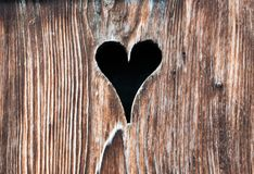 与一个心形的孔的老木门 库存图片