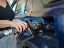 与一个手扶的燃料喷嘴的妇女抽的气体在加油站 免版税库存照片