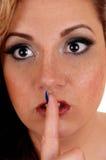 与一个手指的妇女的面孔在嘴 免版税图库摄影