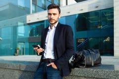 与一个手机的千福年的商人在他的手上 年轻成功的有一个黑皮包的企业时髦的人 库存图片