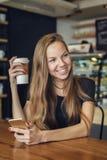 与一个手机的妇女饮用的咖啡在她的手上 免版税图库摄影