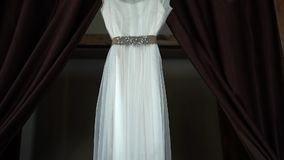 与一个挂衣架的完善的婚礼礼服在新娘的屋子里有棕色帷幕的 股票录像