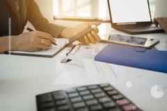 与一个数字式电话的手指触摸屏的商人在桌上的办公室与文件图表数据,商人计算 免版税库存照片
