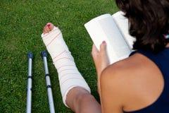 读与一个断腿 免版税库存图片