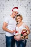 与一个新年圣诞老人帽子和圣诞节玩具熊的年轻人怀孕的家庭 免版税库存图片