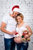与一个新年圣诞老人帽子和圣诞节玩具熊的年轻人怀孕的家庭 库存图片