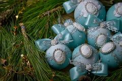 与一个有浮雕的贝壳的蓝色圣诞节球在云杉的分支 免版税库存照片