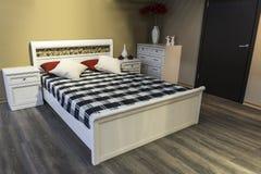 与一个木地板的卧室内部和与床头柜的一个双人床 库存图片
