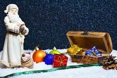 与一个木箱的圣诞快乐-圣诞老人形象有很多礼物和晚上雪背景 免版税库存照片