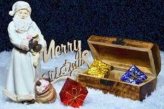 与一个木箱的圣诞快乐-圣诞老人形象有很多礼物和晚上雪背景 库存照片