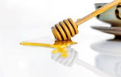 与一个木蜂蜜浸染工的金黄甜蜂蜜在白色ceram 库存图片